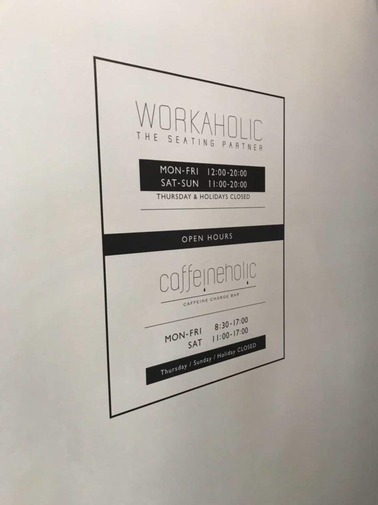WORKAHOLICの壁に描かれているお店の営業時間